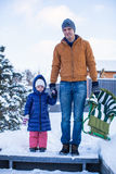 年轻爸爸和小女孩去sledding在寒冷 免版税图库摄影