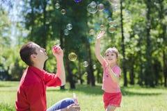 爸爸和他的女儿做泡影 库存照片