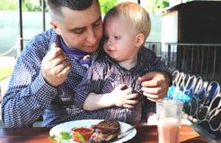 爸爸喂养咖啡馆的孩子 免版税库存图片