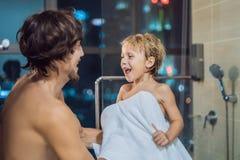 爸爸在一个窗口的背景抹他的儿子与毛巾在一场阵雨以后在晚上在去前睡与a的 库存照片