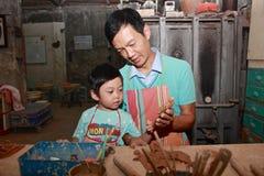 爸爸在与儿子,台北交流道,台湾的瓦器工作 库存图片