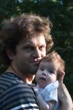 爸爸在公园拿着他的胳膊的一个女儿步行的 春日,家庭步行本质上,晴朗 免版税图库摄影