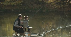 爸爸在好日子鼓励了他的钓鱼的儿子,他们坐桥梁 在红色eepic的射击 股票视频