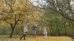 爸爸在秋天公园转动孩子 旋转黄色叶子背景的爸爸一个孩子  免版税库存图片