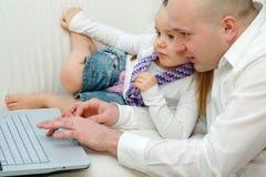 爸爸女儿膝上型计算机 库存图片