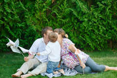 爸爸妈妈和儿子坐一条毯子在公园和亲吻 库存图片