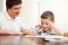 爸爸帮助的儿子执行家庭作业 图库摄影