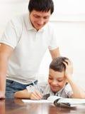 爸爸帮助的儿子执行家庭作业 库存图片