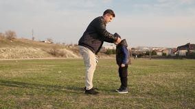 爸爸戴在他的儿子的温暖的黑帽会议并且继续与他的足球比赛户外慢动作 影视素材