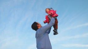 爸爸投掷了婴孩入天空蔚蓝 爸爸投掷婴孩  愉快的家庭的概念 爸爸使用与他的女儿在公园 股票录像