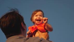 爸爸投掷他的天空蔚蓝的女儿 父亲使用与一个小孩子 使用在晚上的幸福家庭反对 股票视频