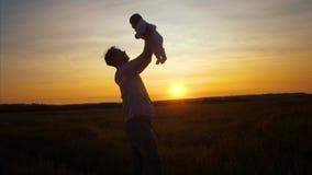 爸爸投掷孩子在金黄太阳日落  慢的行动 股票录像