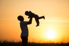 爸爸投掷婴孩在日落 免版税库存照片