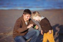 爸爸显示一个玩具给他的小儿子 免版税库存照片