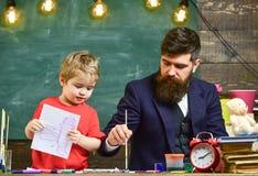 爸爸显示儿子如何使用水彩 逗人喜爱的孩子在他的手上的拿着一张图画 大厦概念创造性墙壁的现有量lego 图库摄影