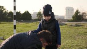 爸爸栓鞋带给他的儿子并且显示他如何做在足球慢动作的一张通行证 股票视频