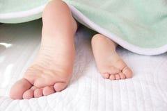 爸爸的大脚和小孩儿子的微小的脚 免版税库存照片