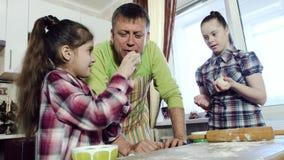 爸爸获得与他的女儿的乐趣,当烹调面团在他的家庭厨房时 股票视频