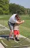 爸爸高尔夫球儿子教学 免版税图库摄影