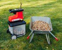 爽朗的庭院,与独轮车的电切菜机mulcher有很多木腐土 库存图片