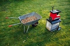 爽朗的庭院,与独轮车的电切菜机mulcher有很多木腐土 免版税库存照片
