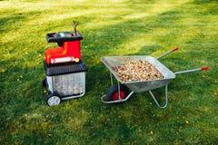 爽朗的庭院,与独轮车的电切菜机mulcher有很多木腐土 库存照片