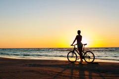 片刻时间 在多彩多姿的运动的妇女骑自行车者剪影 免版税图库摄影