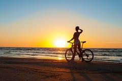 片刻时间 在多彩多姿的运动的妇女骑自行车者剪影 免版税库存照片