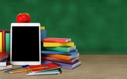 片剂、五颜六色的书、学校用品和苹果在桌o上 免版税图库摄影