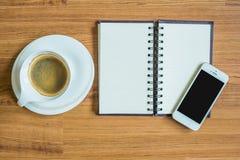 片剂、巧妙的电话、笔记和咖啡在木纹理背景 库存照片