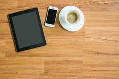 片剂、巧妙的电话、笔记和咖啡在木纹理背景 免版税图库摄影