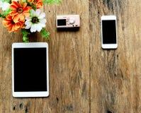 片剂、照相机、电话和花在花瓶在老木桌上 免版税库存图片