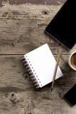 片剂、电话、笔记薄和咖啡在木桌上 免版税图库摄影