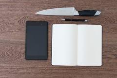 片剂、笔记本、笔和一把刀子在一张木桌上 ag暴力 免版税库存图片