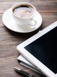 片剂、纸笔记本和咖啡在桌上 免版税图库摄影