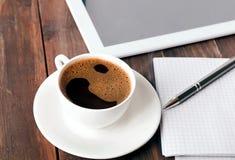 片剂、纸笔记本和咖啡在桌上 库存照片