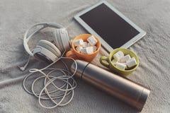 片剂、耳机、热水瓶和蛋白软糖在一个杯子在一块灰色布料 库存图片