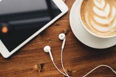 片剂、耳机和热奶咖啡与拿铁艺术 免版税库存照片