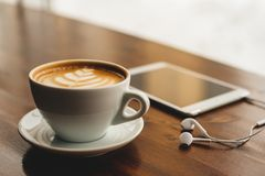 片剂、耳机和热奶咖啡在咖啡馆 库存图片