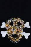 片剂、药片和胶囊,塑造一块蠕动的头骨 隔绝在与拷贝空间的黑背景 免版税库存照片