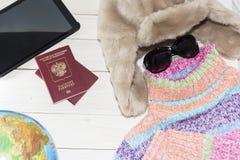 片剂个人计算机与一个明亮的颜色毛线衣和温暖的帽子 是时间离开 俄国游人 免版税图库摄影