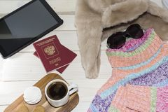 片剂个人计算机与一个明亮的颜色毛线衣和温暖的帽子 是时间离开 俄国游人 图库摄影