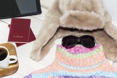 片剂个人计算机与一个明亮的颜色毛线衣和温暖的帽子 是时间离开 免版税库存照片