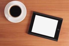 片剂个人计算机和咖啡。 免版税库存图片