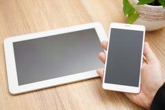片剂个人计算机和手机在手中 库存图片