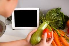 片剂个人计算机在厨房里 库存图片
