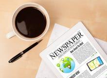 片剂个人计算机显示在屏幕上的新闻有一杯咖啡的在书桌上的 免版税库存照片