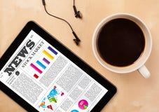 片剂个人计算机显示在屏幕上的新闻有一杯咖啡的在书桌上的 库存图片