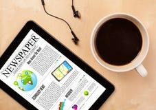 片剂个人计算机显示在屏幕上的新闻有一杯咖啡的在书桌上的 免版税库存图片
