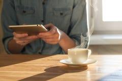 从片剂个人计算机的读书新闻在早晨 免版税图库摄影